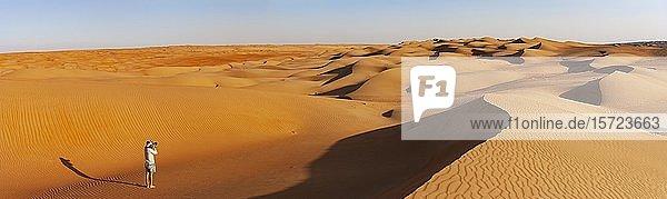 Panorama  Mann fotografiert in der Wüste  Sanddünen  Wüste Rimal Wahiba Sands  Oman  Asien
