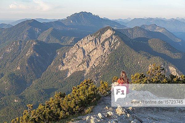 Junge Frau sitzt am Gipfel  Ausblick vom Herzogstand  auf Jochberg und Alpen  Oberbayern  Bayern  Deutschland  Europa