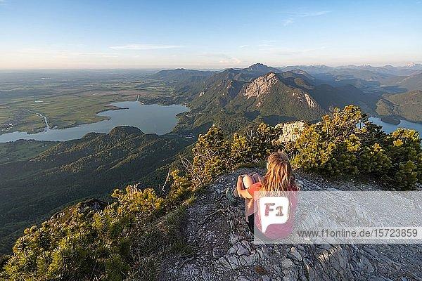 Junge Frau sitzt am Gipfel  Ausblick vom Herzogstand auf Kochelsee  Jochberg und Walchensee  Alpenvorland  Alpen  Oberbayern  Bayern  Deutschland  Europa