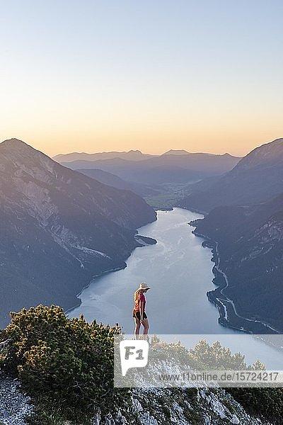 Sonnenuntergang  junge Frau blickt über Berglandschaft  Ausblick vom Berg Bärenkopf auf den Achensee  links Seebergspitze und Seekarspitze  rechts Rofangebirge  Tirol  Österreich  Europa