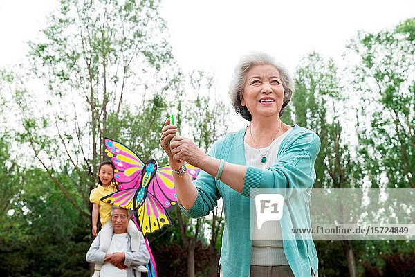 Older couples with a granddaughter is flying a kite in the park