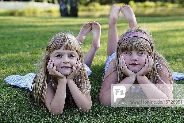 Zwei Mädchen  Geschwister liegen auf der Wiese mit aufgestütztem Kopf  6 und 7 Jahre  Portrait  Tschechien  Europa