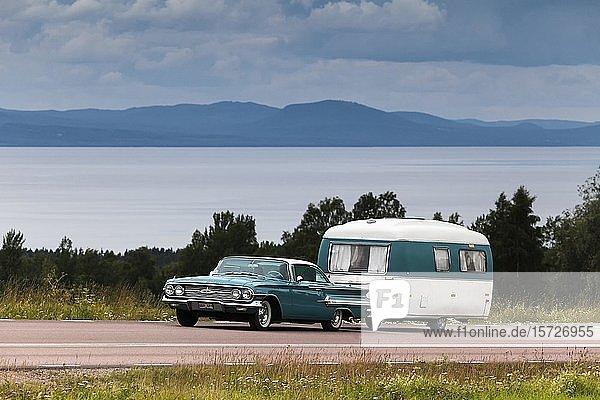 Amerikanischer Oldtimer  Chevrolet Impala Coupe Baujahr 1960  mit Retro-Wohnwagen  hinten der Siljan-See  bei Rättvik  Dalarna  Schweden  Europa