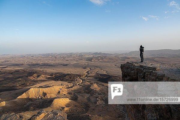 Tourist standing on rock at Maktesh Ramon Crater  Israel  Asia