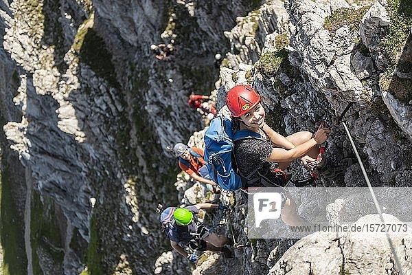 Gruppe an Bergsteigern mit Helm an einem gesicherten Klettersteig  Mittenwalder Höhenweg  Karwendelgebirge  Mittenwald  Deutschland  Europa