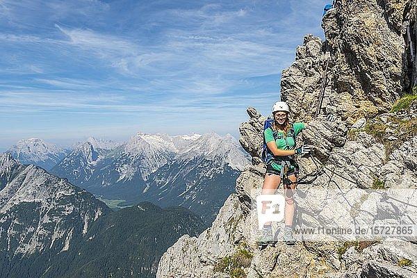 Bergsteigerin  junge Frau mit Kletterausrüstung steht an einem Felsen  gesicherter Klettersteig  Mittenwalder Höhenweg  Karwendelgebirge  Mittenwald  Deutschland  Europa