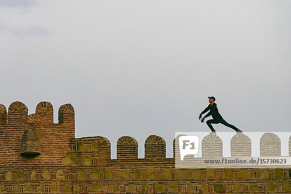 Tbilisi  Georgia A man dangerously performs yoga moves on top of the Narikala Fortress over the old town.