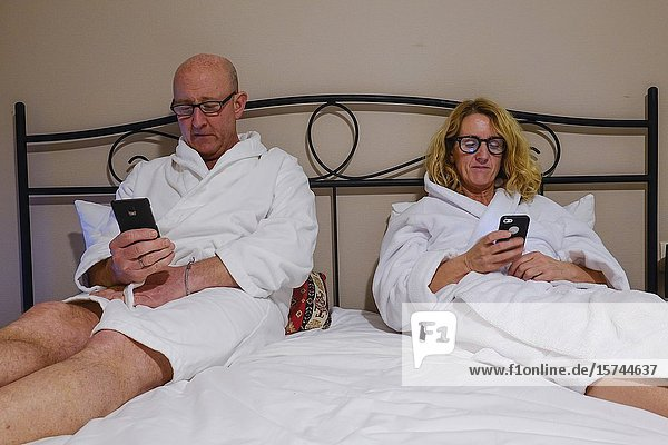 Tbilisi  Georgia A middle aged couple in bed with white bathrobes reading their phones.