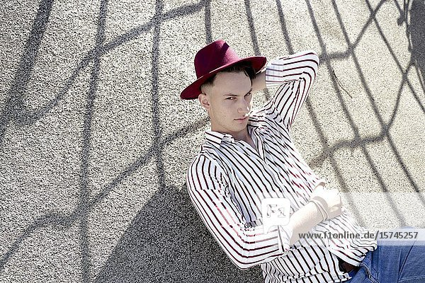 Man wearing hat  lying on the floor. Munich  Germany.