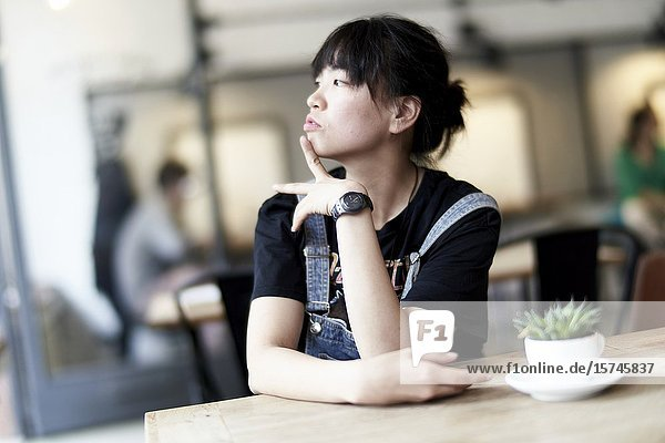 Korean woman sitting at table in cafe  in front of cup filled with leaves.
