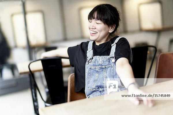 Korean woman sitting at table in cafe  laughing.
