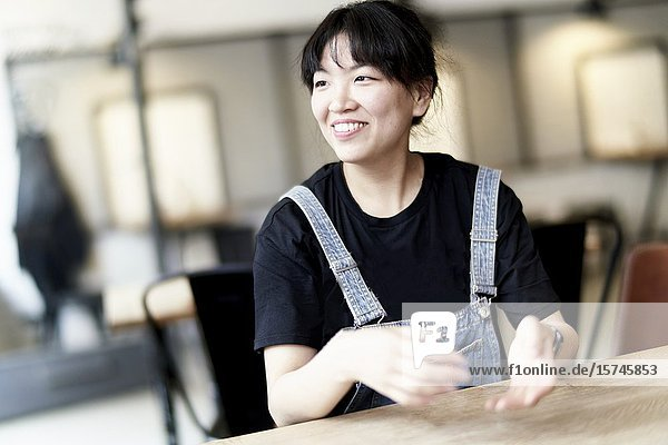 Korean woman sitting at table in cafe  moving hands