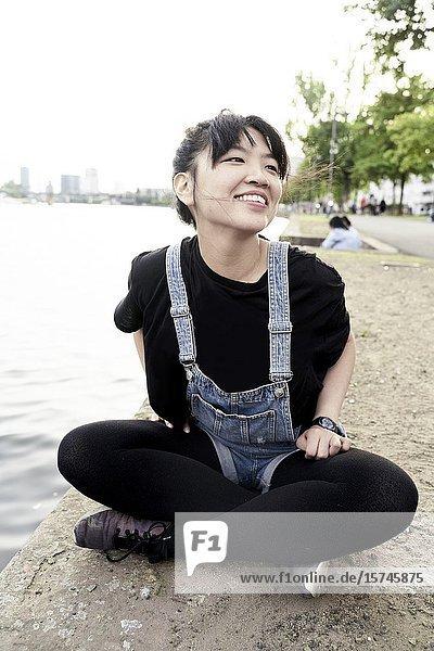 Korean woman sitting by water. Frankfurt am Main  Germany.