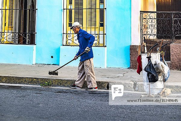 Local Cuban man cleaning the streets of Cienfuegos  Republic of Cuba  Caribbean  Central America.