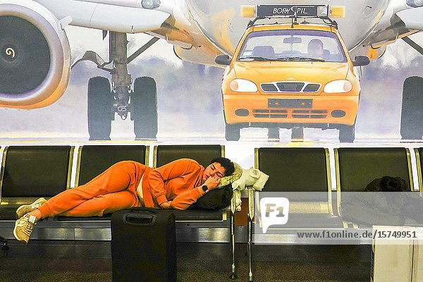 Kyiv  Ukraine A woman sleeps on a bench at the Borispol airport under a poster showing a car and a plane.