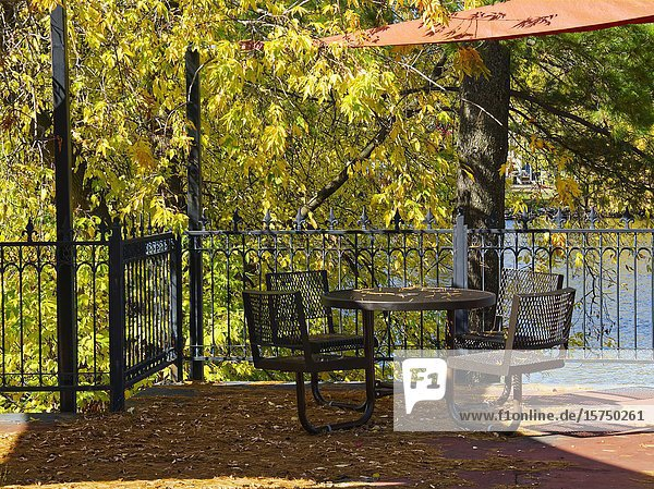 Table and chairs beside Mississippi River in autumn  Carleton Place  Ontario  Canada.