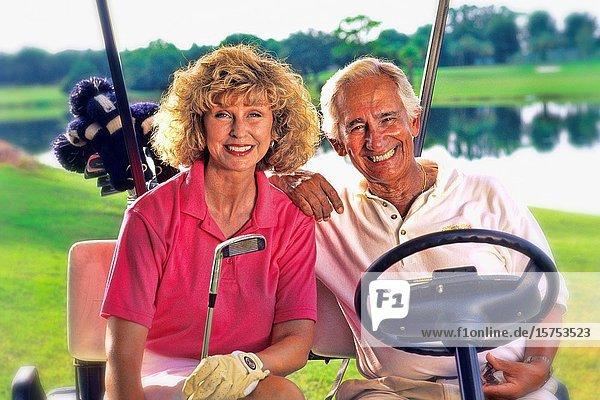 Active senior couple in golf cart playing game of golf