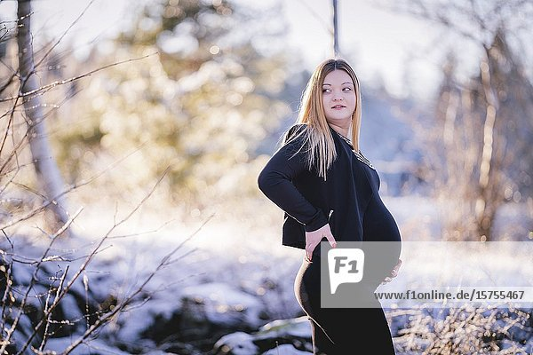 Portrait of a young pregnant girl soon to become mother  posing in Swedish winter landscape shot with natural light.