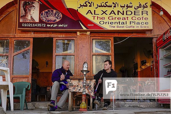 Siwa Oasis  Egypt Swedish tourists at a coffee shop enjoying a water pipe  a game of backgammon and a turkish coffee.