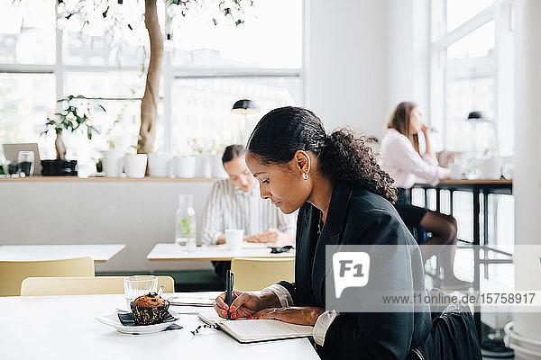 Geschäftsfrau schreibt Tagebuch  während sie einen Muffin in der Büro-Cafeteria isst
