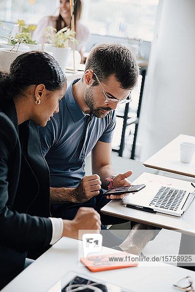 Männliche und weibliche Kollegen diskutieren am Bürotisch am Smartphone