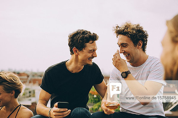 Happy man showing mobile phone to friend having drink at terrace during party