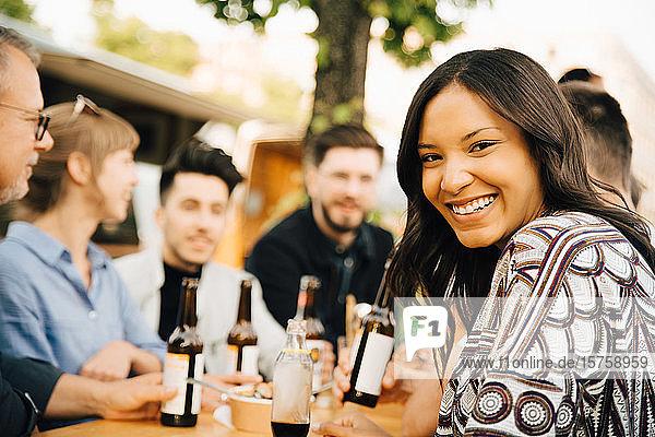 Porträt einer lächelnden jungen Frau  die mit Freunden zusammensitzt und sich am geselligen Beisammensein erfreut