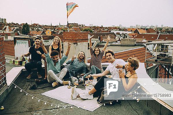 Glückliche männliche und weibliche Freunde jubeln auf der Terrasse  während sie sich auf der Dachparty in der Stadt amüsieren