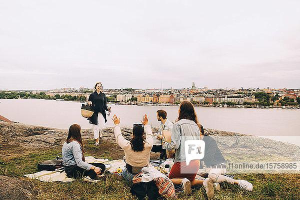 Freunde begrüssen Frau  die auf dem Feld am See gegen den Himmel läuft