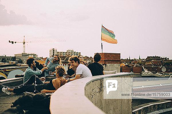 Freunde genießen Dachfeier in Stadt gegen Himmel