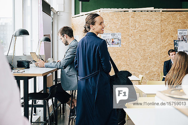 Smiling businesswoman with bag looking away while standing amidst colleagues in coworking space
