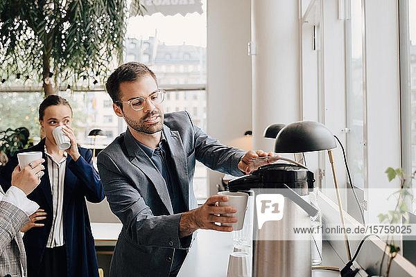 Geschäftsmann trinkt in der Pause Kaffee mit Kolleginnen im Kreativbüro