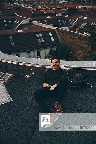 Hochwinkel in voller Länge eines glücklichen jungen Mannes  der sich während einer Party in der Abenddämmerung auf der beleuchteten Terrasse entspannt