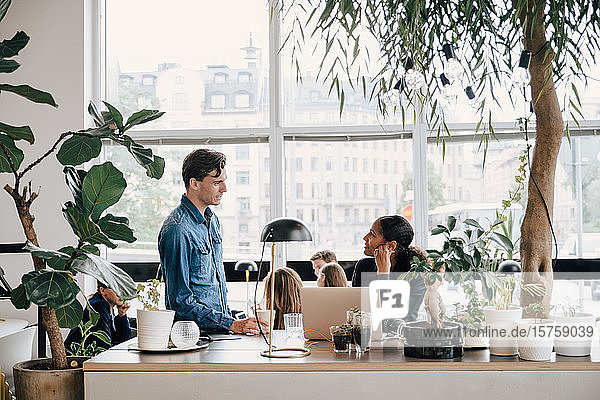 Junge Geschäftskollegen diskutieren am Schreibtisch im Kreativbüro