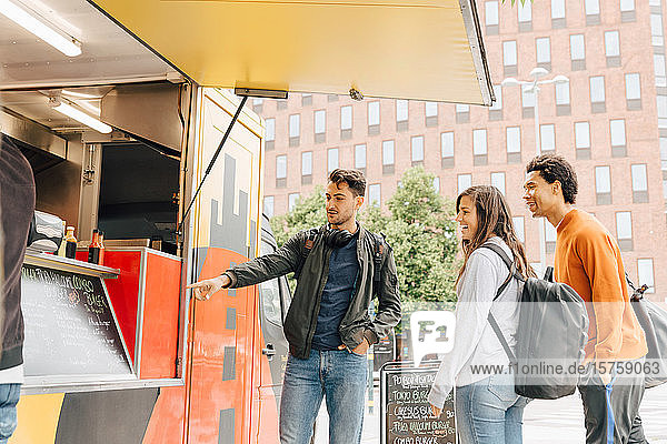 Young man pointing at menu while standing with friends by food truck in city