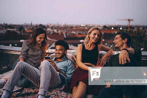 Paare entspannen gemeinsam auf der Terrasse in der Stadt während einer Dachparty
