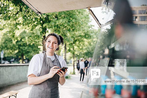 Glücklicher junger Besitzer benutzt Smartphone  während er am Speisewagen steht