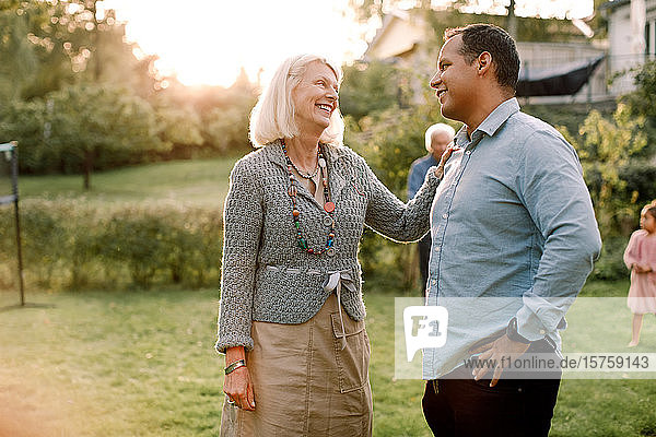 Smiling mother talking with son while standing in backyard