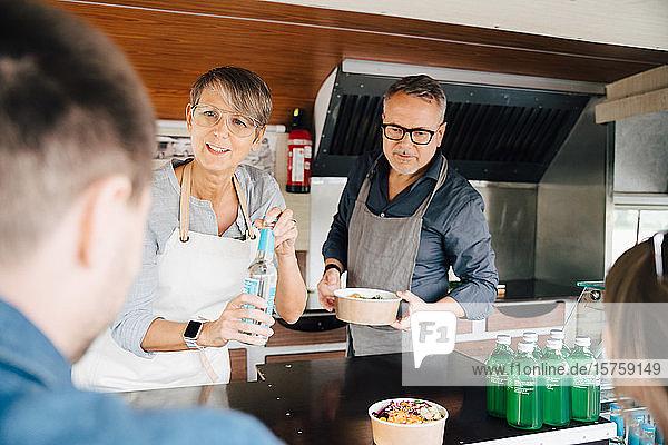 Reife Besitzer  die Kunden Speisen und Getränke servieren  während sie im Nutzfahrzeug stehen