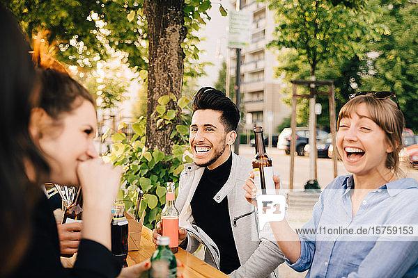 Lachende Freunde und Freundinnen beim Sitzen mit Getränken bei der Gartenparty