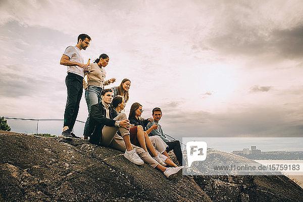 Männliche und weibliche Freunde genießen Picknick am Seeufer bei Sonnenuntergang