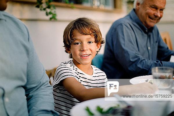 Porträt eines lächelnden Jungen  der während des Mittagessens mit seiner Familie am Esstisch sitzt