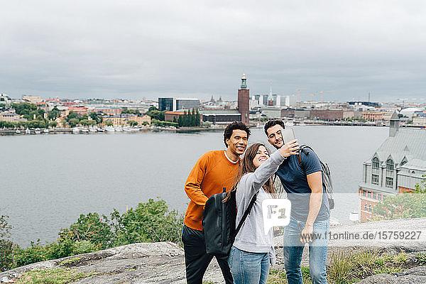 Lächelnde Freunde  die sich mit dem Handy selbstständig machen  während sie am Fluss in der Stadt gegen den Himmel stehen
