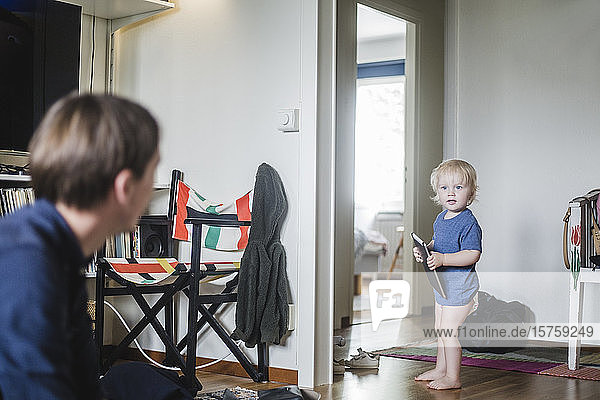 Full length of baby boy holding digital tablet while looking at father in living room