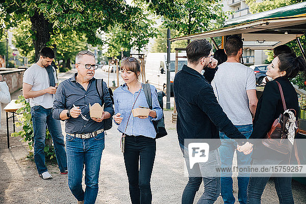 Male and female customer with box talking while couple holding hands and standing by food truck