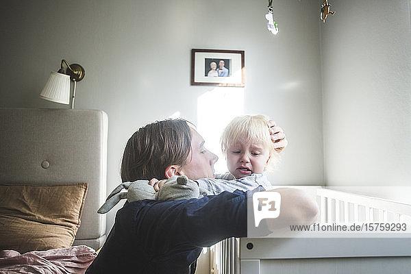 Vater tröstet weinendes blondes Baby in der Krippe mit zärtlicher Liebe zu Hause