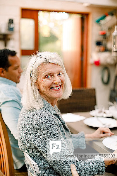 Portrait of smiling senior woman sitting with son at dining table in home
