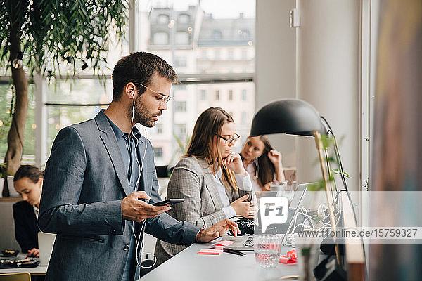 Männlicher Fachmann benutzt Laptop und Smartphone bei der Arbeit mit Kollegen am Coworking Space