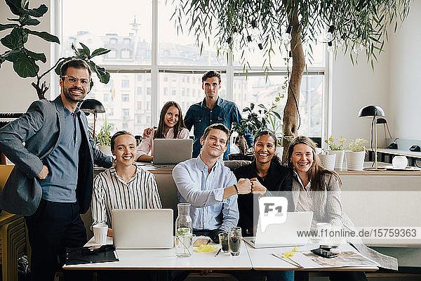 Selbstbewusste männliche und weibliche Kollegen mit Laptops am Schreibtisch im Kreativbüro