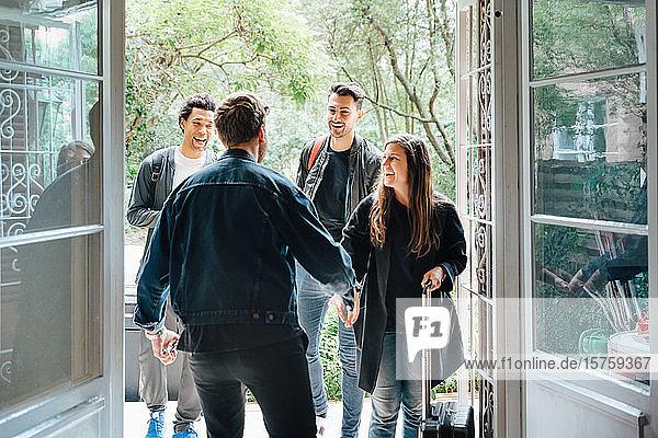 Rückansicht des Händeschüttelns des Eigentümers mit Gästen  die in der Tür stehen